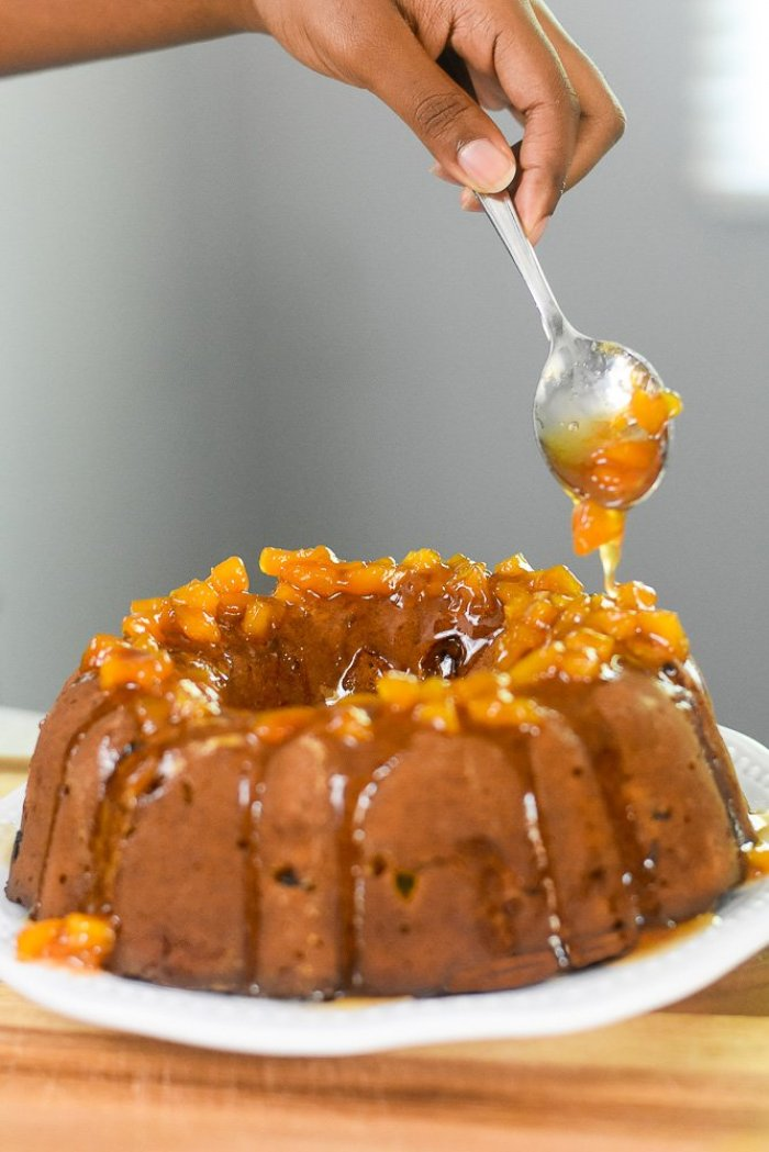 drizzling peach honey glaze over top of honey peach pound cake