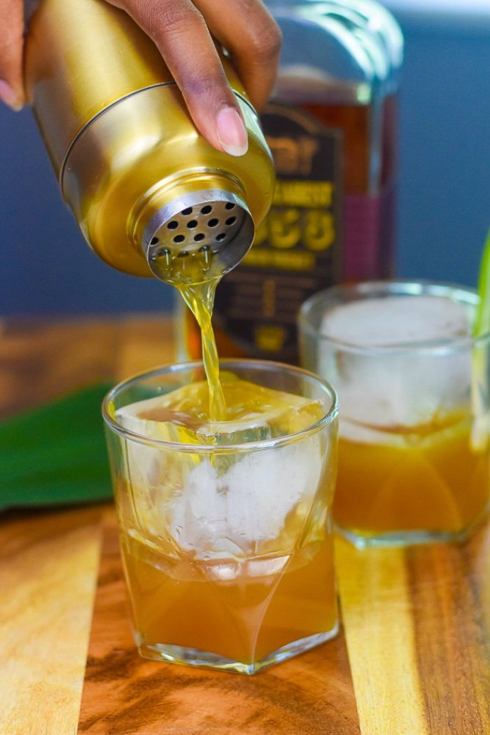 pouring brown sugar pineapple whiskey sipper from cocktail shaker over ice