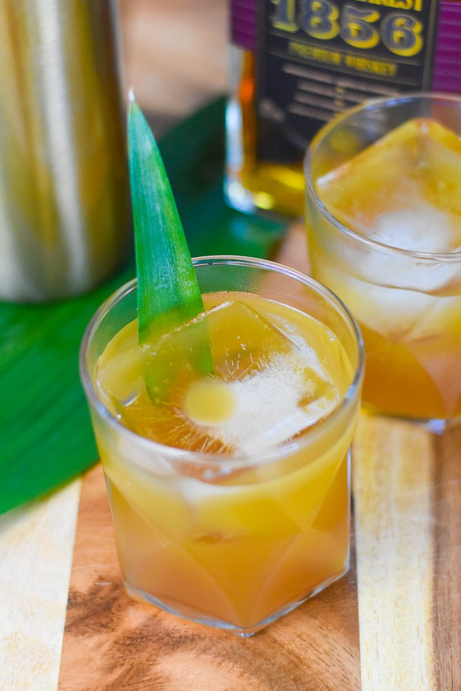 two whiskey pineapple cocktails in geometric glasses