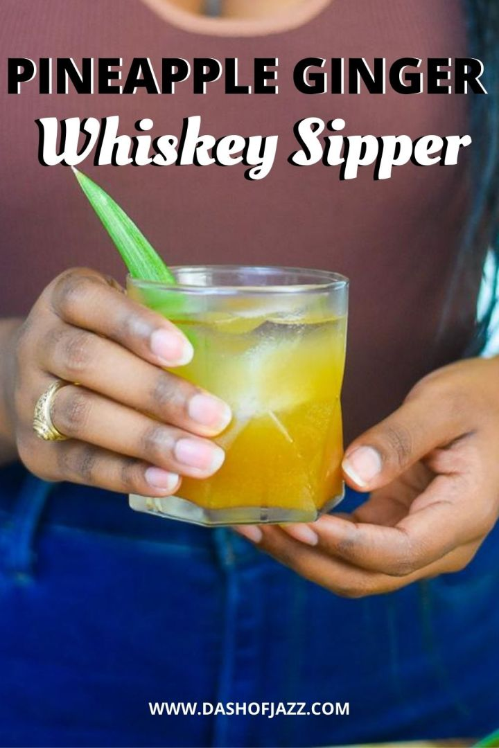 """holding whiskey cocktail with text overlay """"pineapple ginger whiskey sipper"""""""