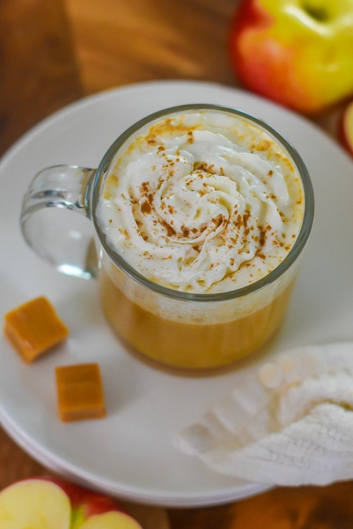 whipped cream melting into mug of hot spiked cider