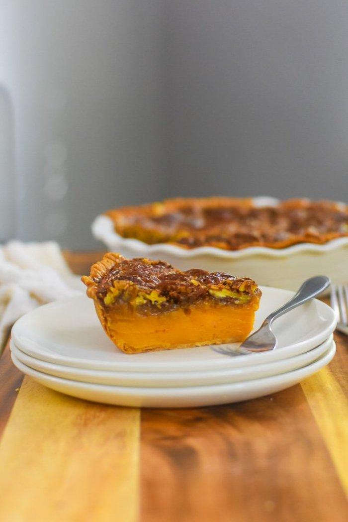 slice of bourbon sweet potato pecan pie on stack of plates