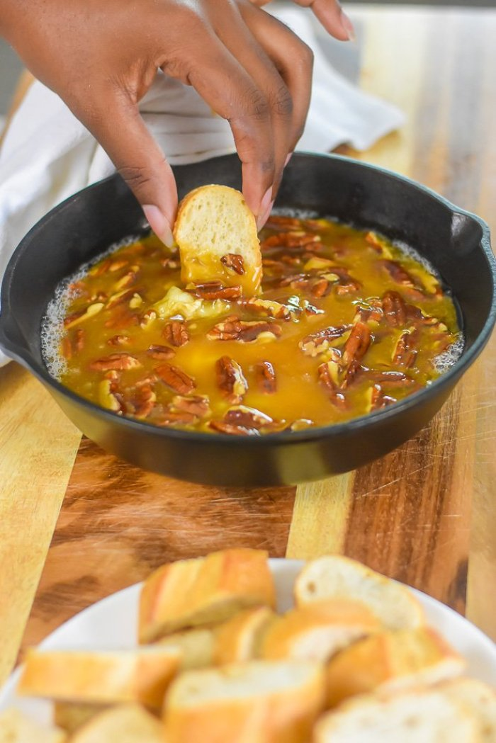 dipping crusty French bread into praline baked brie dip