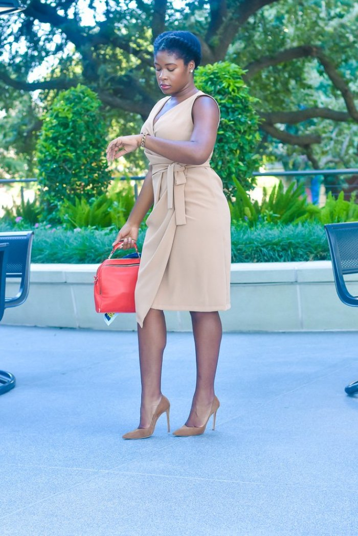 Jazzmine standing outdoors looking down at watch, wearing camel wrap dress, and natural hair in simple flat twist.