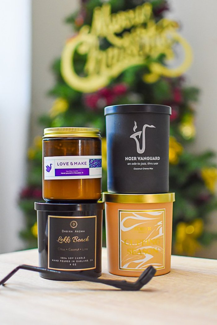 four candles from Black-owned brands stacked on table top