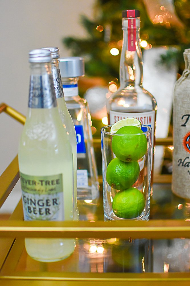 ginger beer and fresh limes displayed on bar cart
