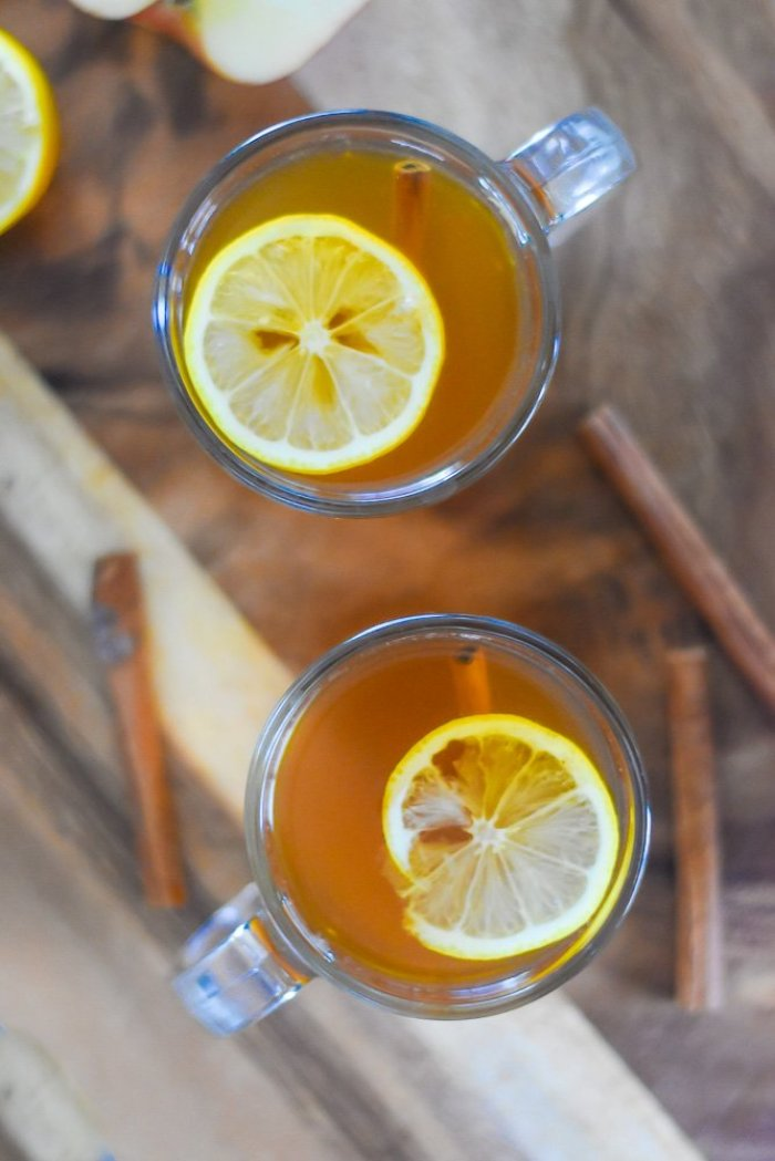 lemon slices floating in clear mugs of hot toddies