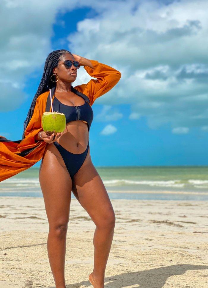 Jazzmine standing on beach holding fresh coconut and straw