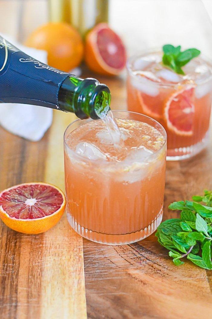 pouring champagne into blood orange bourbon smash