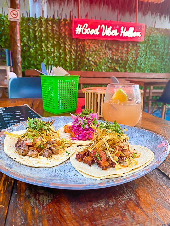 """plate of three tacos on table top with neon sign in background reading """"#Good Vibes Holbox"""""""