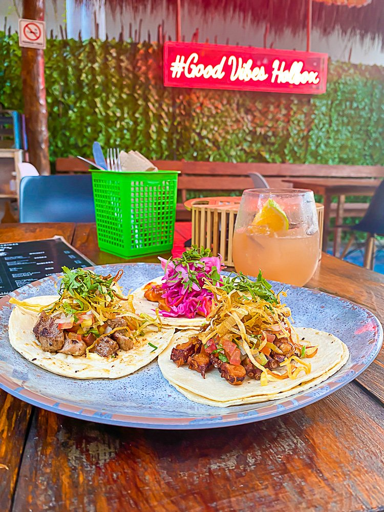 "plate of three tacos on table top with neon sign in background reading ""#Good Vibes Holbox"""