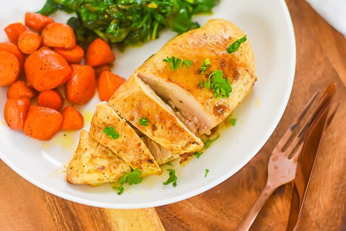 cut chicken breast on plate with carrots and spinach.