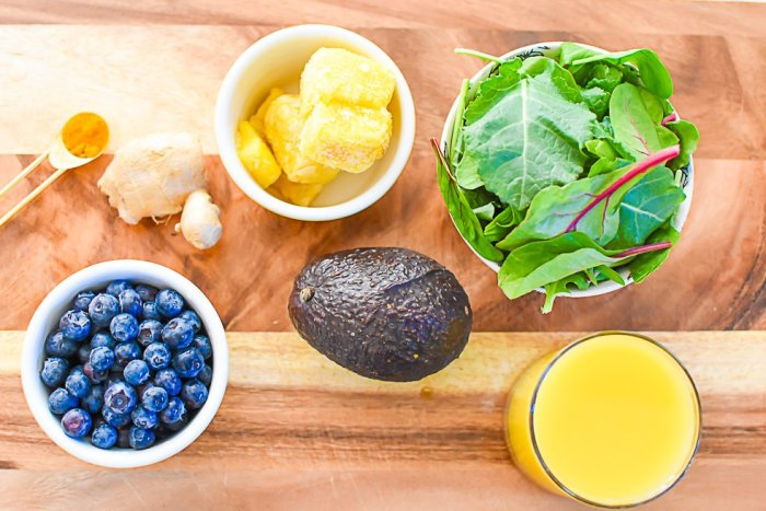 super greens mix, frozen pineapple, fresh ginger, blueberries, avocado, orange juice, and spoon of ground turmeric on wooden cutting board