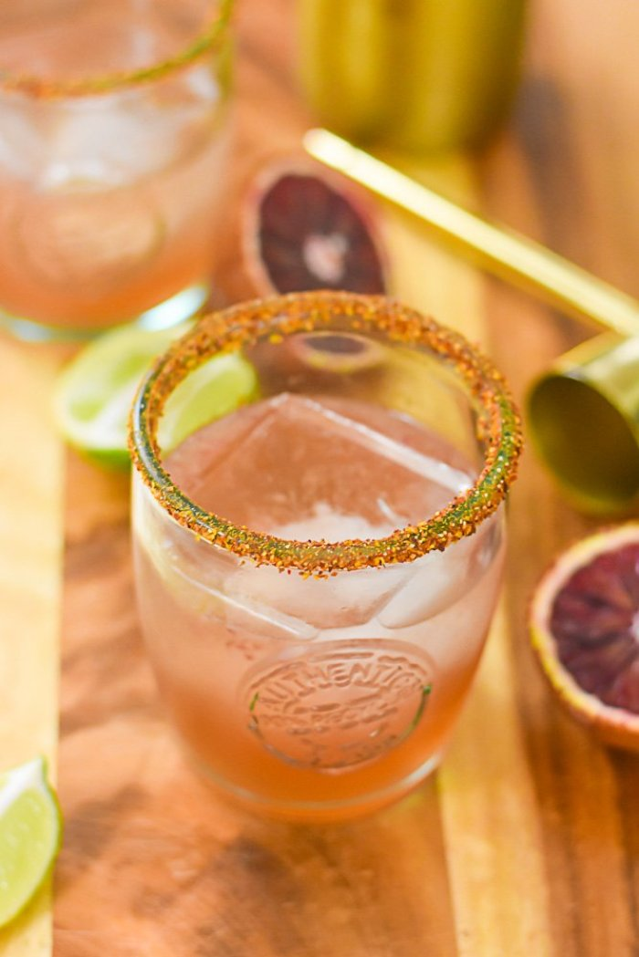 two blood orange mezcal margaritas surrounded by fresh blood oranges and lime wedges.