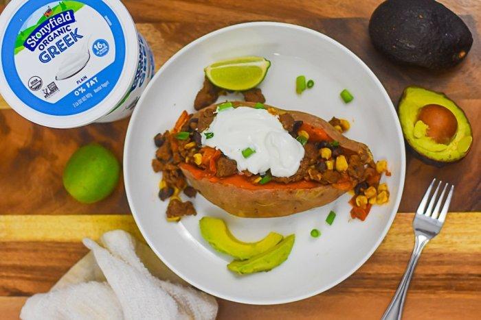 sweet potato stuffed with taco filling on plate next to fresh limes, avocados, and tub of Greek yogurt.