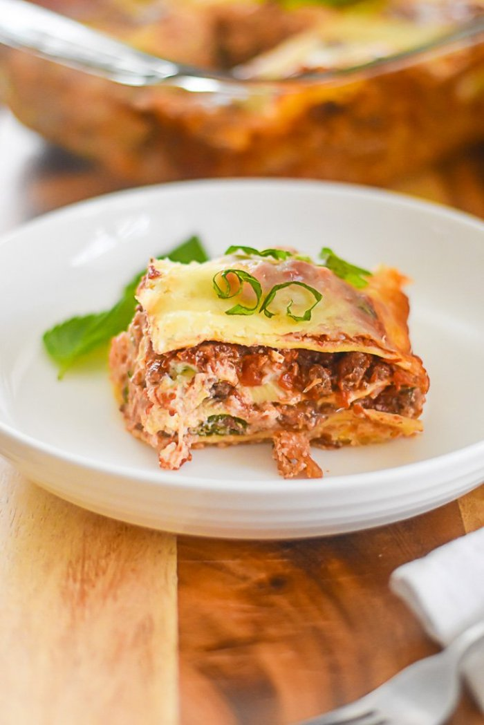 piece of three cheese lasagna on plate, garnished with fresh basil.