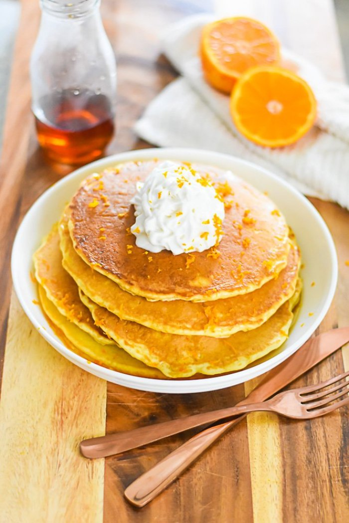 stack of mimosa pancakes on plate, fresh orange, bottle of syrup, fork and knife on wooden surface.
