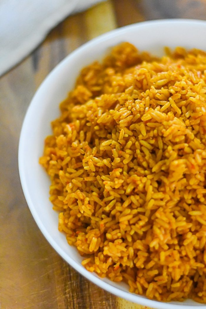 plate of Nigerian-style jollof rice on wooden cutting board.