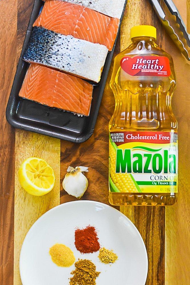 raw salmon filets, corn oil, fresh lemon, garlic, and spices on countertop.