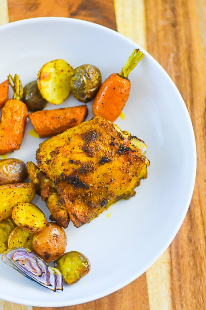 roasted chicken thigh, baby potatoes, red onion, and carrots on a white plate.
