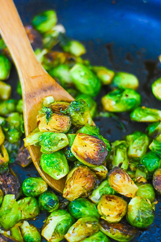 sautéed brussels sprouts in pan on wooden spoon.