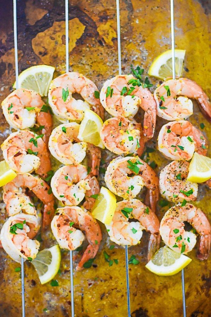 lemon pepper shrimp skewers on a sheet pan.