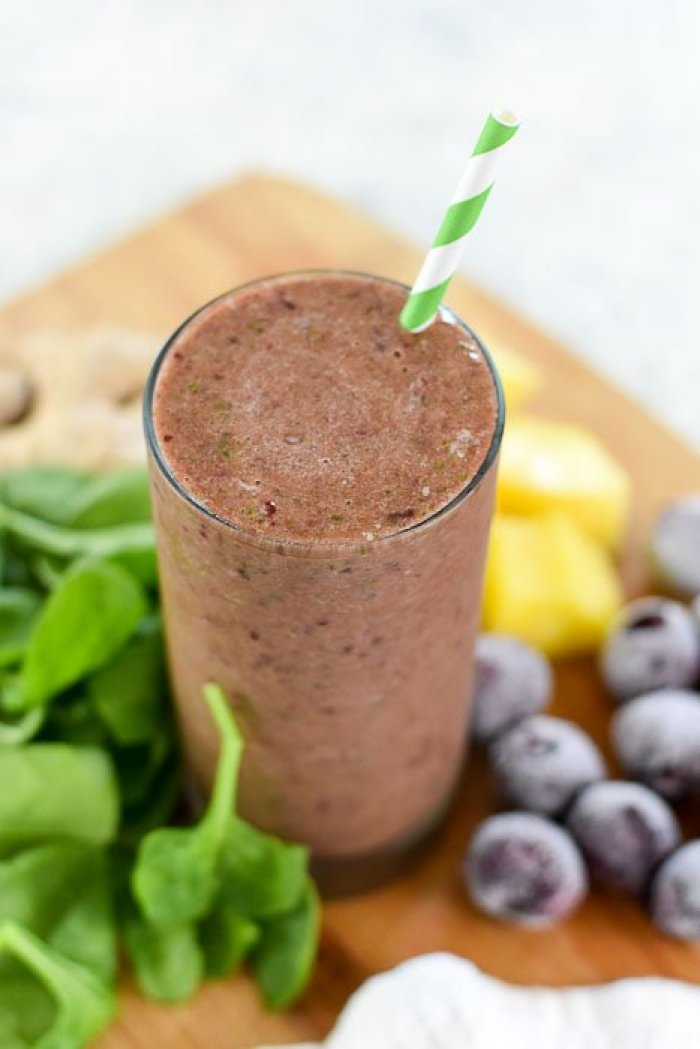 cherry pineapple and ginger smoothie in glass with green paper straw