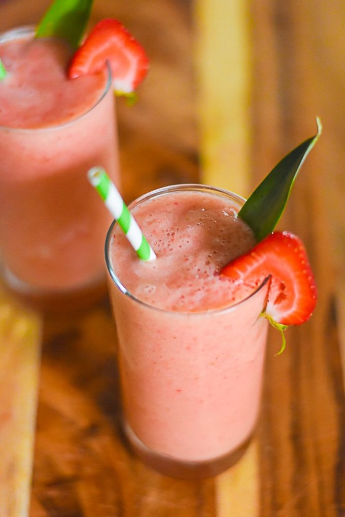 two glasses of frosé garnished with fresh strawberry slices, pineapple fronds, and green striped paper straws.
