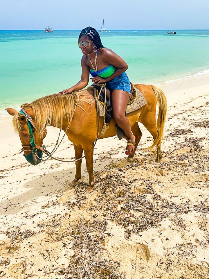 Jazzmine petting horse on Cozumel beach.