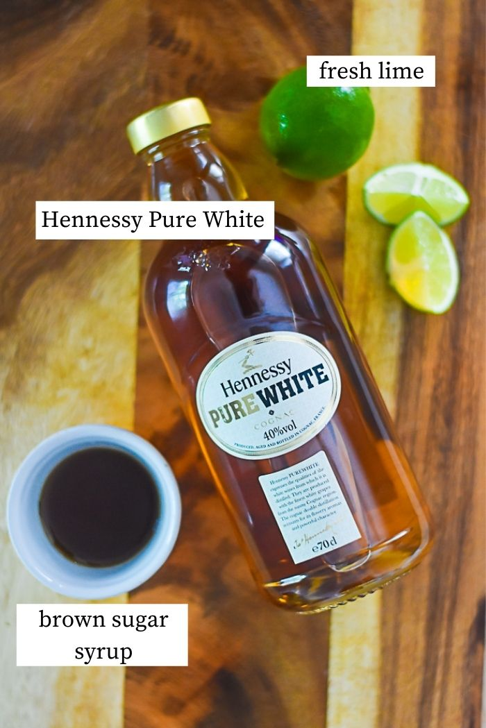 flat lay of bottle of hennessy pure white, brown sugar simple syrup, and fresh lime on cutting board.