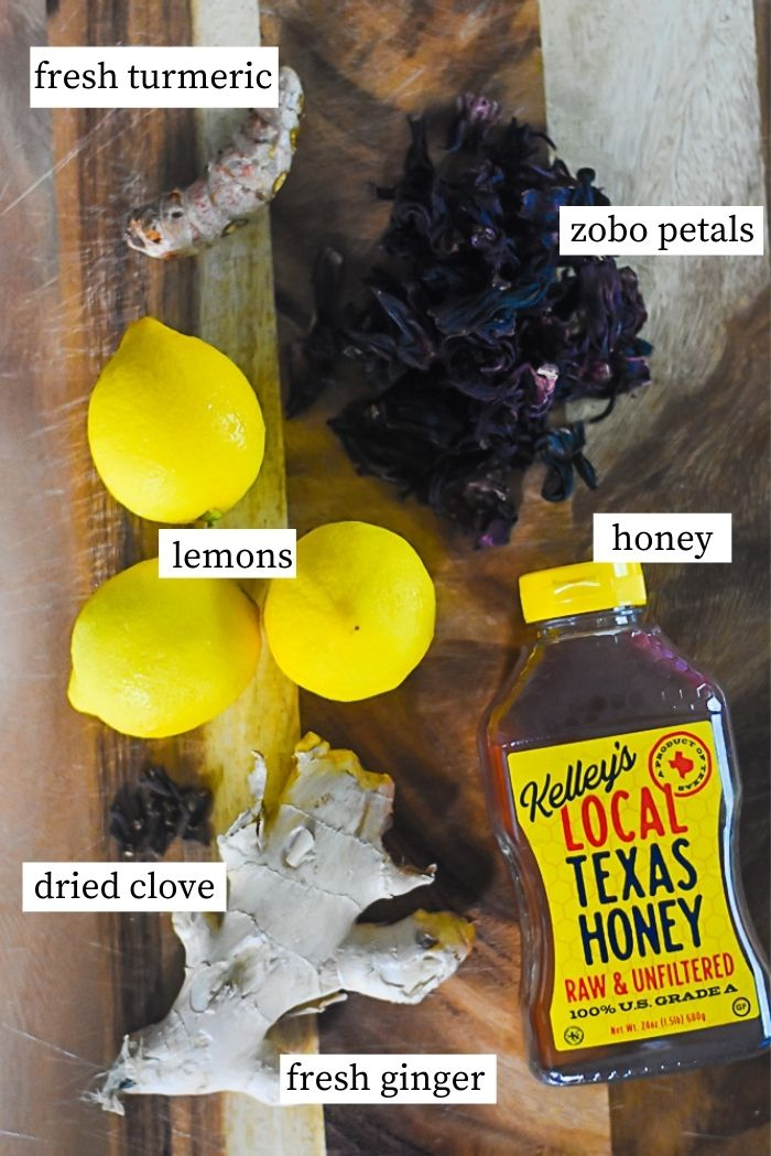 flat lay of zobo lemonade ingredients: bottle of honey, knob of fresh ginger, dried clove buds, knob of fresh turmeric, lemons, and dried hibiscus petals.