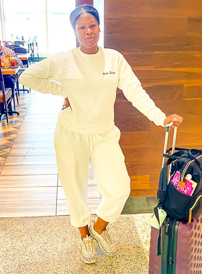 Jazzmine standing in airport wearing all white sweat suit and leopard sneakers.