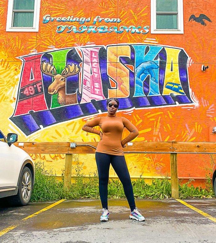 "Jazzmine standing in front of ""Greetings from Fairbanks, Alaska"" mural."
