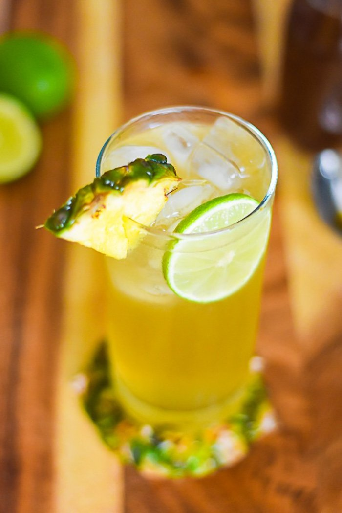spiced pineapple gin and tonic cocktail garnished with wedge of fresh pineapple.