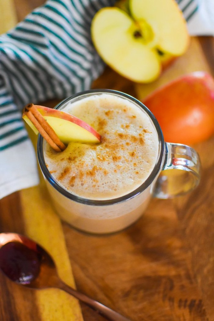 fancy homemade apple chai latte garnished with apple slice and cinnamon stick.
