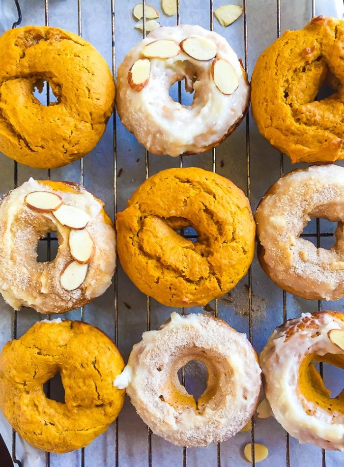 frosted pumpkin cake donuts on cooling rack.
