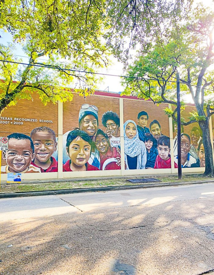 wall mural outside elementary school depicted diverse group of children and adults.