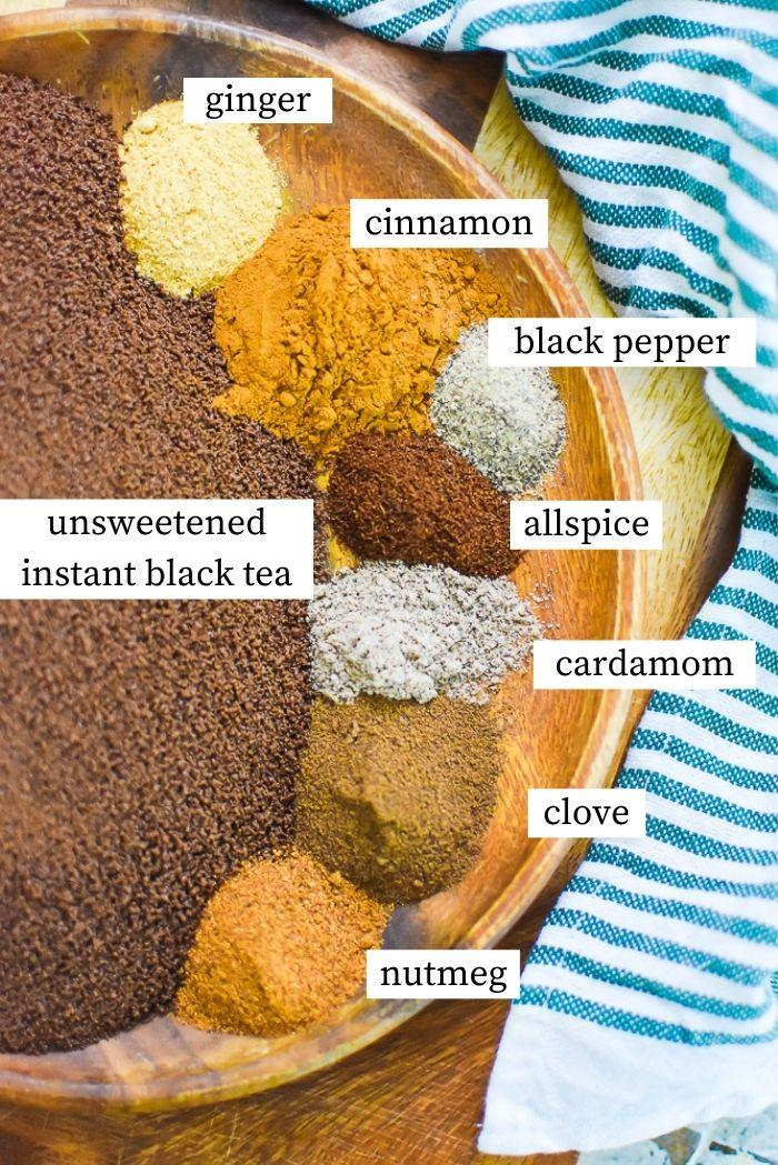 labeled photo of ingredients for instant chai powder: instant black tea, nutmeg, clove, cardamom, allspice, black pepper, cinnamon, ginger.