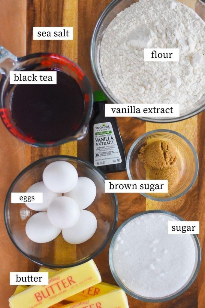 sweet tea pound cake ingredients on wooden cutting board: butter, eggs, sugar, brown sugar, vanilla extract, flour, sea salt, and black tea.