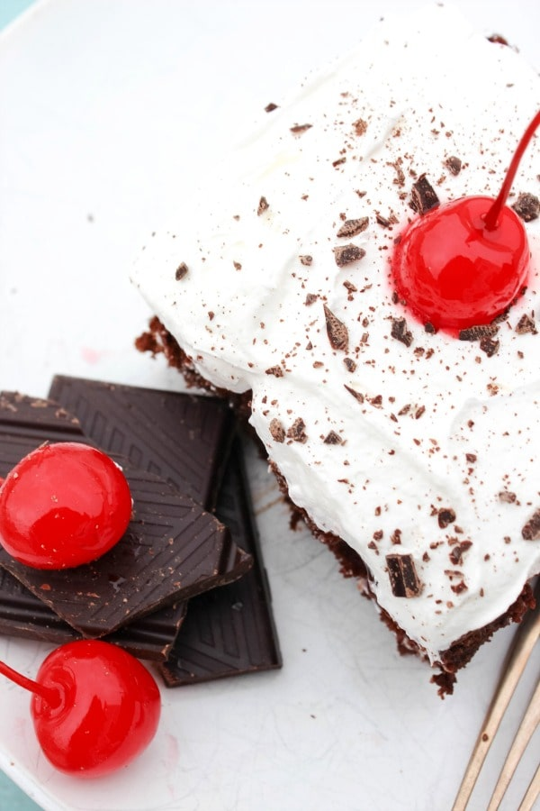 BBlack Forest Poke Cake is a rich chocolate-fudge cake. This chocolate cherry torte will melt in your mouth as you savor every gooey fudge filled bite. slices of chocolate next to cake slice, white counter