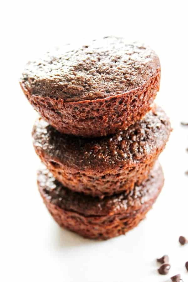 Double Chocolate Banana Quinoa Muffins are a delicious source of protein, iron, and whole grains. These muffins will quickly become a family favorite.- Stacked muffins, white table