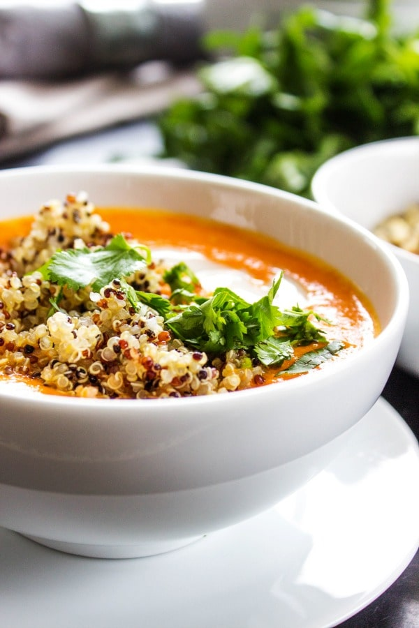 Thai Curry Red Pepper Quinoa Soup is an easy 30-minute mealmade with red curry, coconut milk and quinoa.Skip take-out and make this healthy twist instead.- White bowl, white plate, herbs, grey napkin, wooden table