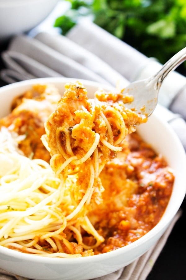 SLOW COOKER CHICKEN PARMESAN - A FAVORITE ITALIAN CLASSIC MADE EASY, WHILE TASTING JUST AS DELICIOUS.- White bowl, metal fork, grey napkins, herbs on table