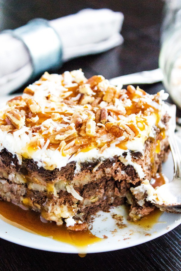 GERMAN CHOCOLATE ICEBOX CAKE - White plate, wooden table, grey napkin, metal fork