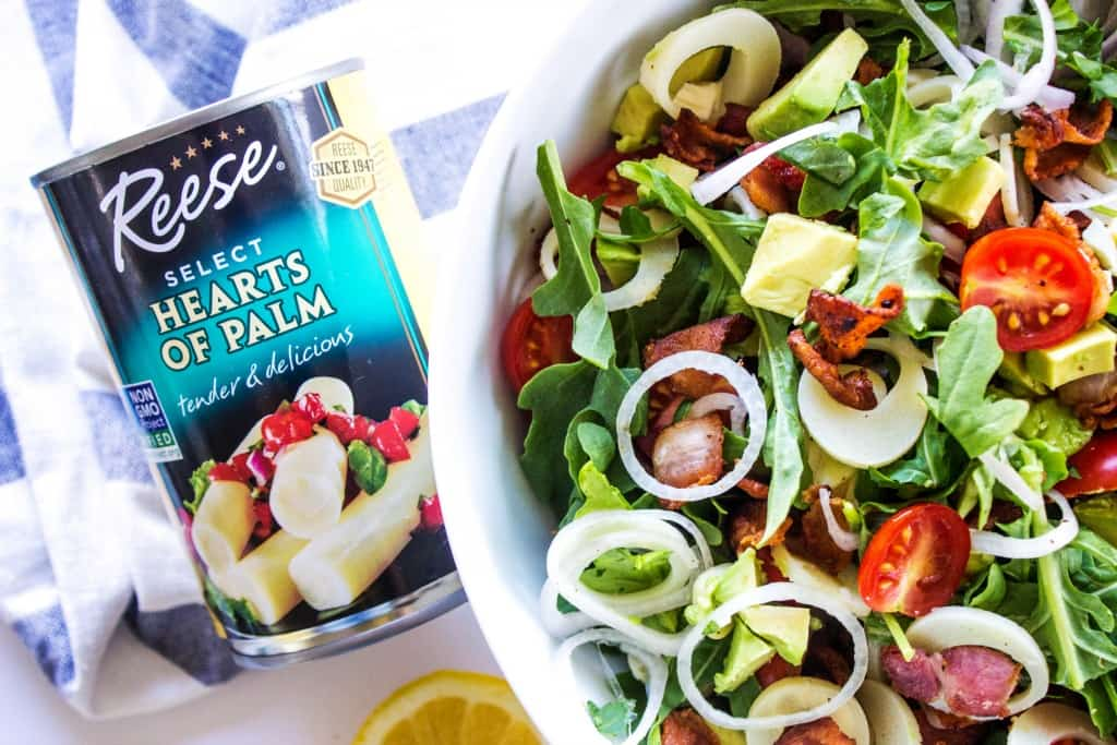 ARUGULA AND HEARTS OF PALM SALAD Can of Hearts of Palm, white bowl, white and blue napkin