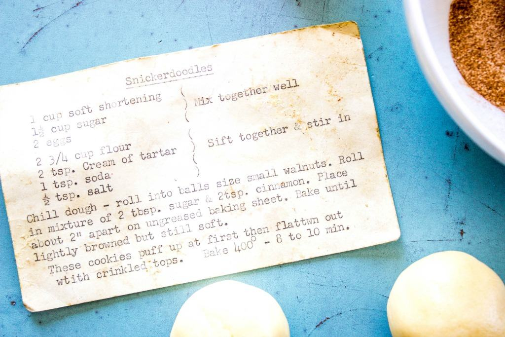 BEST EVER SNICKERDOODLE COOKIE RECIPE - Original recipe card on blue tray with cinnamon and raw cookies dough