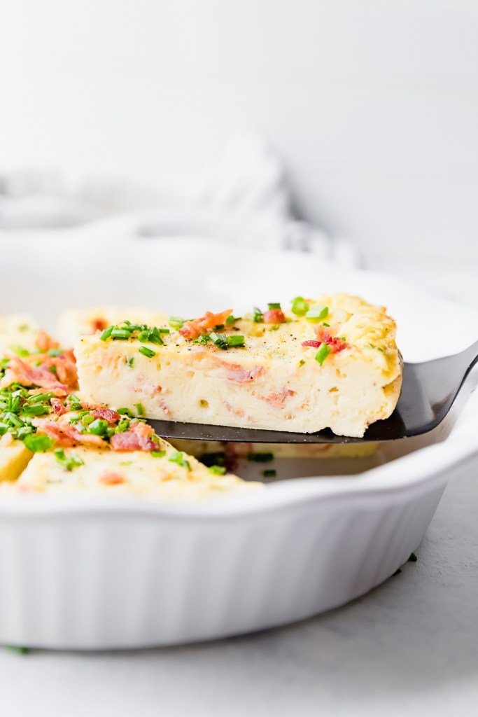 A lightened up recipe on a brunch classic this Bacon Chive Crustless Quiche is simple, easy and delicious. Adding bacon makes everything incredible.