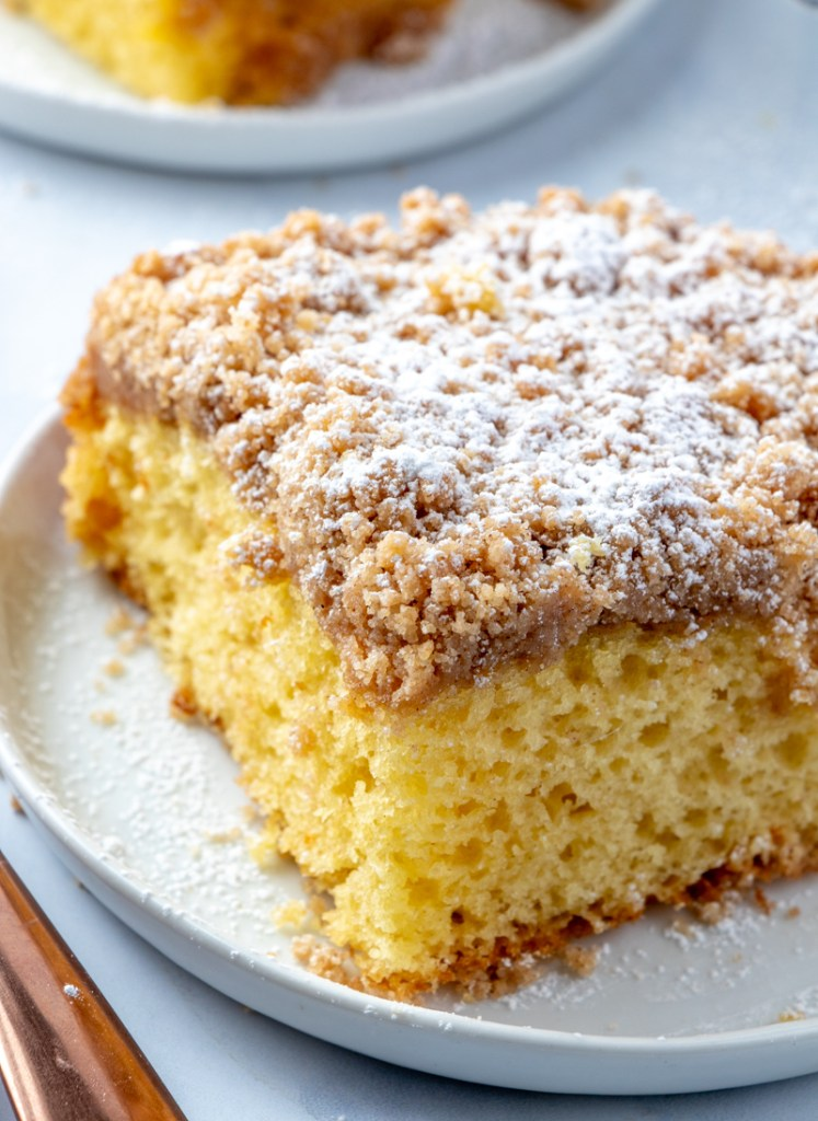 coffee cake on white plate with streusel topping and powdered sugar