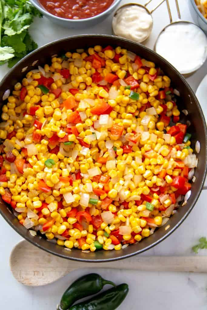 skillet filled with corn, red bell peppers, onions and jalapenos