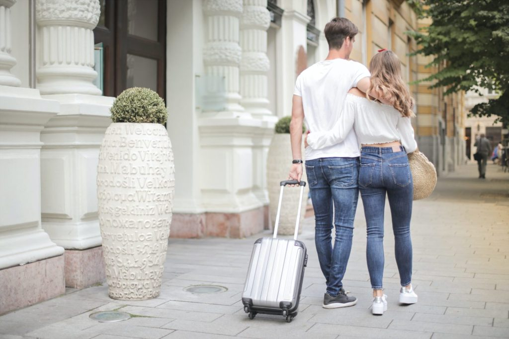 Vacationing as a Couple: man and woman walking down the street holding suitcase